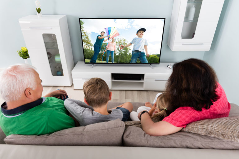 66444815 - family with kids watching movie on tv together at home