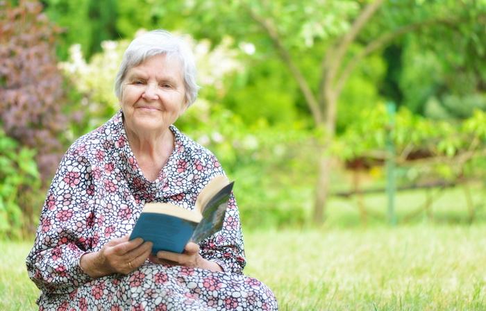 Senior woman reading book in park.